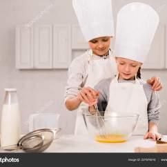 Kitchen Apron For Kids Oak Cabinet 孩子们在厨房的桌子上戴着围裙和厨师帽在碗里搅拌鸡蛋 图库照片 孩子们在厨房的桌子上戴着围裙和厨师帽在碗里