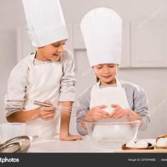 Kitchen Apron For Kids Sconces 孩子们在厨房餐桌上准备食物时有选择地关注围裙和厨师帽的孩子们 图库 孩子们在厨房餐桌上准备食物时有选择地关注围裙和厨师