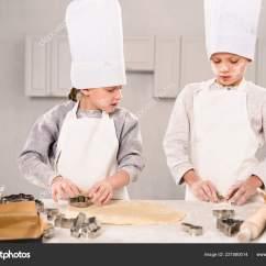 Kitchen Hats Cabinet Refinishing Phoenix 小兄弟和妹妹在厨师帽子和围裙的选择性焦点切割面团饼干在桌子在厨房 照片作者allaserebrina