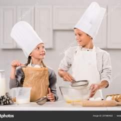 Kitchen Apron For Kids French Country Chairs 在厨房的桌子上准备的小孩子们穿着围裙的围裙和厨师帽 图库照片 在厨房的桌子上准备的小孩子们穿着围裙的围裙和厨师
