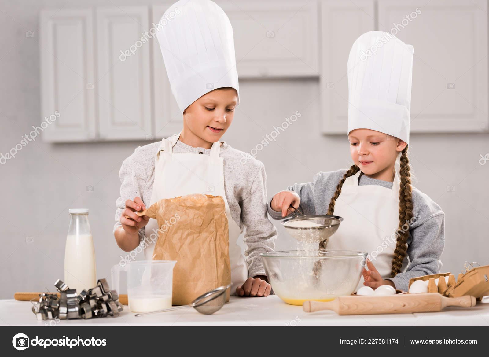 kitchen apron for kids chair cushions with ties 快乐的孩子在围裙筛选面粉通过筛子到碗在桌子在厨房 图库照片