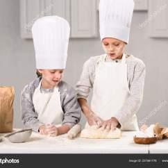 Kitchen Apron For Kids Sink Cabinets Lowes 孩子们在厨房的桌子上用滚针做面团的围裙和厨师帽 图库照片 孩子们在厨房的桌子上用滚针做面团的围裙和厨师