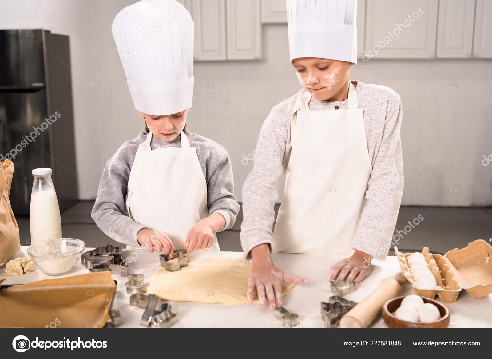 kitchen apron for kids grease trap 孩子们在厨师帽和围裙上切割面团饼干在厨房的桌子高角度的看法 图库照片 孩子们在厨师帽和围裙上切割面团饼干在厨房的桌子高