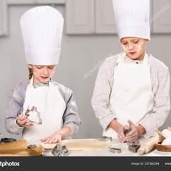 Kitchen Apron For Kids Ikea Cabinets Prices 孩子们戴着厨师帽和围裙在厨房的桌子上切面团做饼干 图库照片 孩子们戴着厨师帽和围裙在厨房的桌子上切面团做