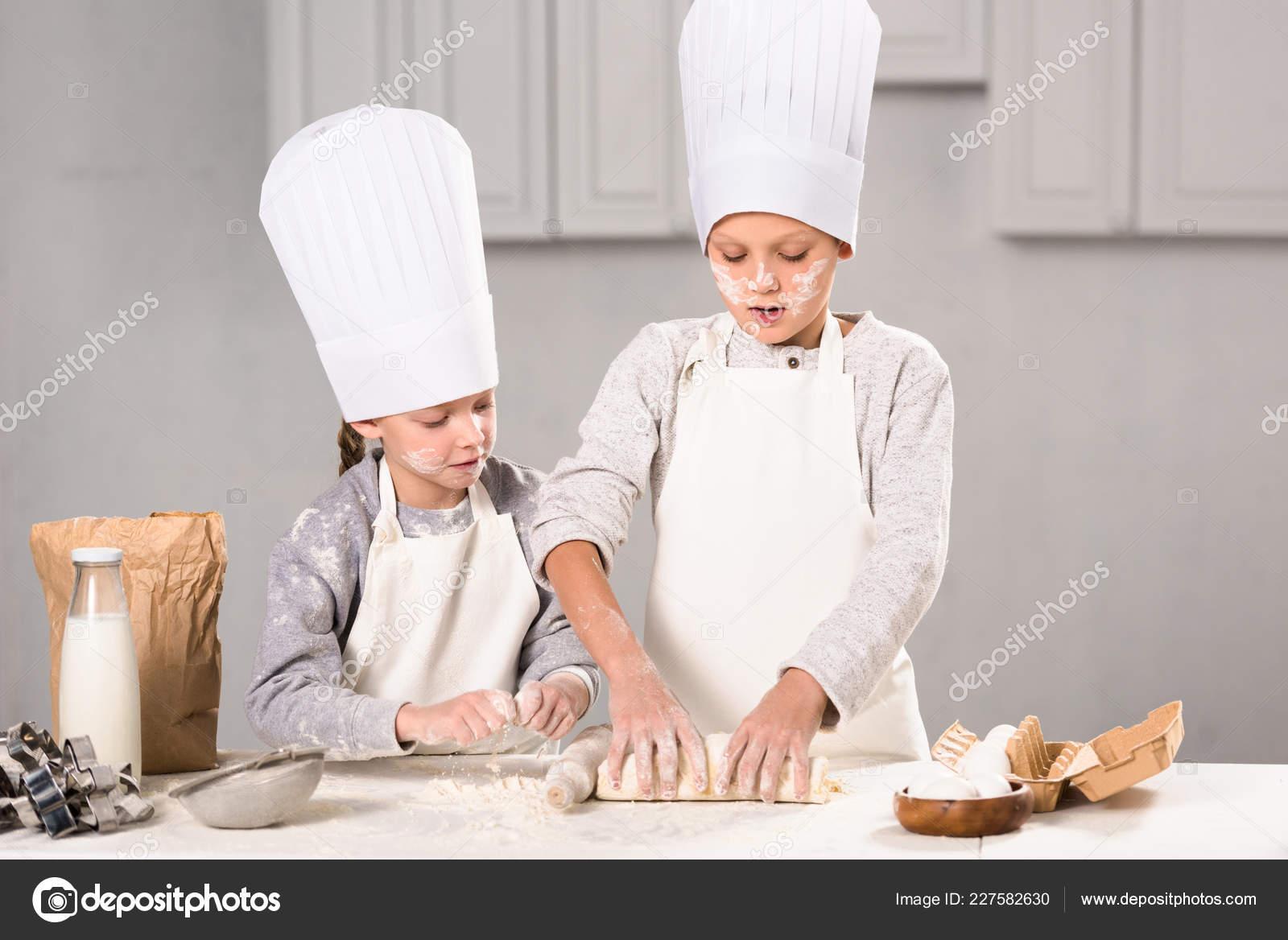 kitchen apron for kids mixer reviews 专注的孩子在围裙和厨师帽与滚针面团在厨房的桌子 图库照片