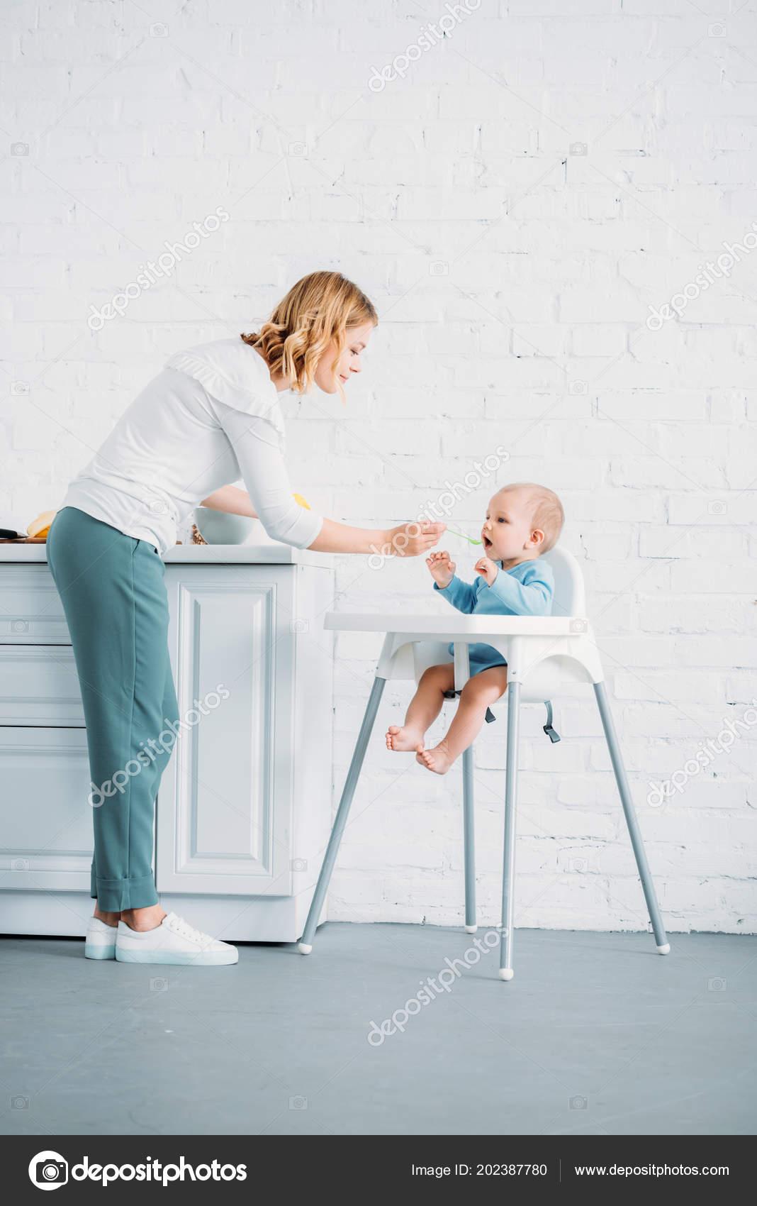 kitchen dining chairs menards kitchens 母亲喂养她的小孩而他坐在厨房的餐椅在家 图库照片 c andrewlozovyi 图库