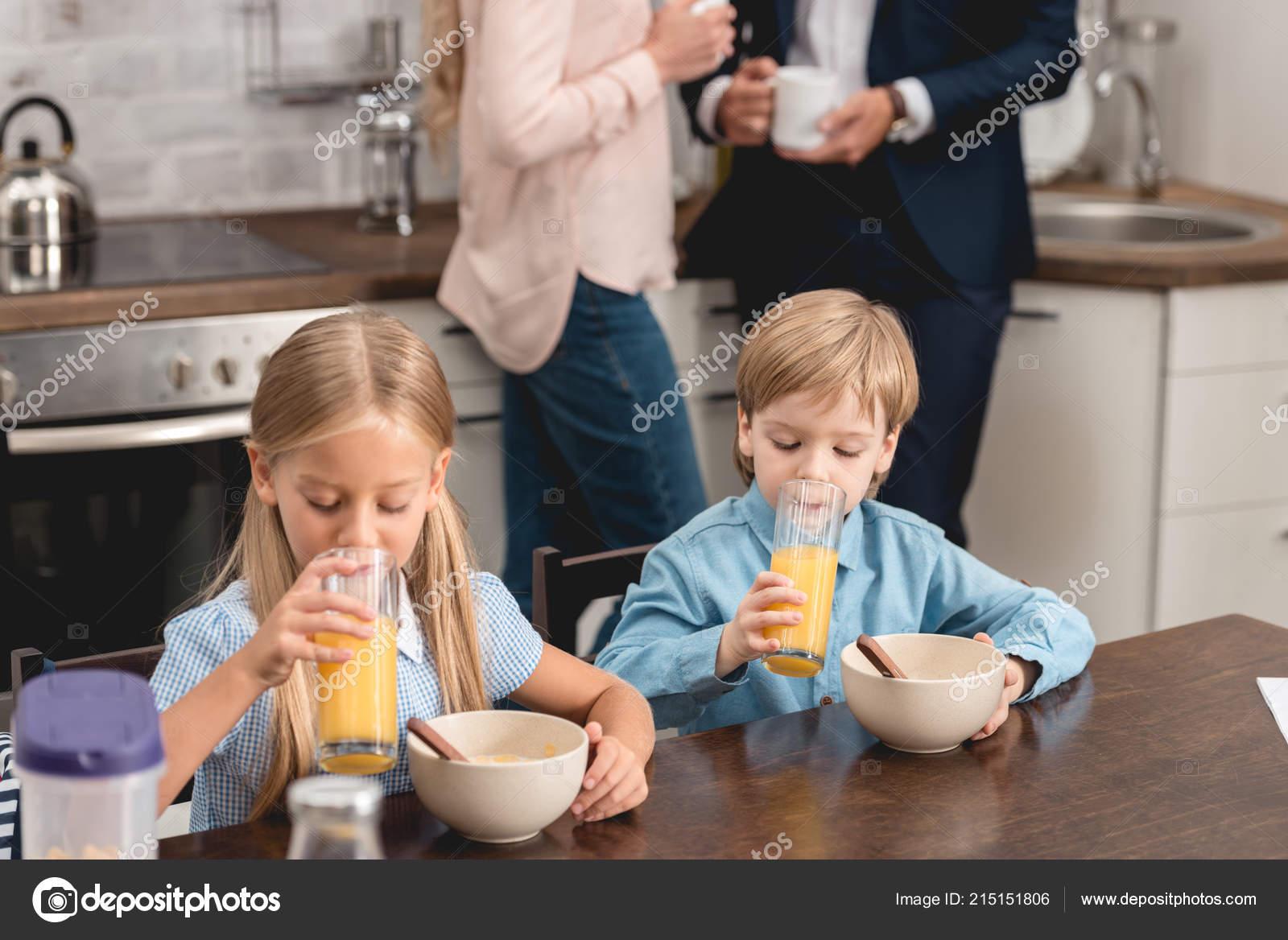kitchen kid wall art for 可爱的小孩子们一起在厨房吃早饭而父母喝咖啡的背景 图库照片