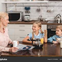 Kitchen Kid Lights Under Cabinets 快乐的母亲有一杯咖啡而坐在厨房与孩子在早餐 图库照片 C Andrewlozovyi 图库