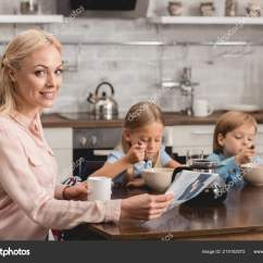 Kitchen Kid Large Trash Can 微笑的母亲有一杯咖啡而坐在厨房与孩子在早餐和看相机 图库照片 微笑的母亲有一杯咖啡而坐在厨房与孩子在早餐和看