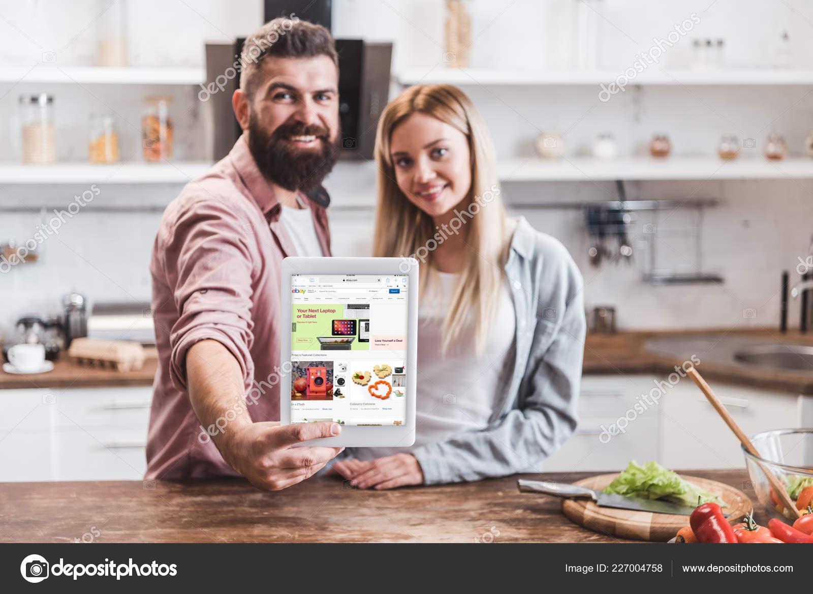 ebay kitchen king cabinets 夫妇拿着数字平板电脑与易趣应用程序在屏幕上在厨房 图库社论照片