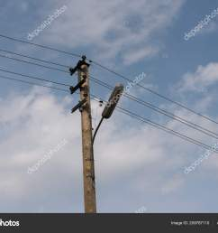 wooden street lamp post electric wires blue sky white clouds stock photo [ 1600 x 1168 Pixel ]