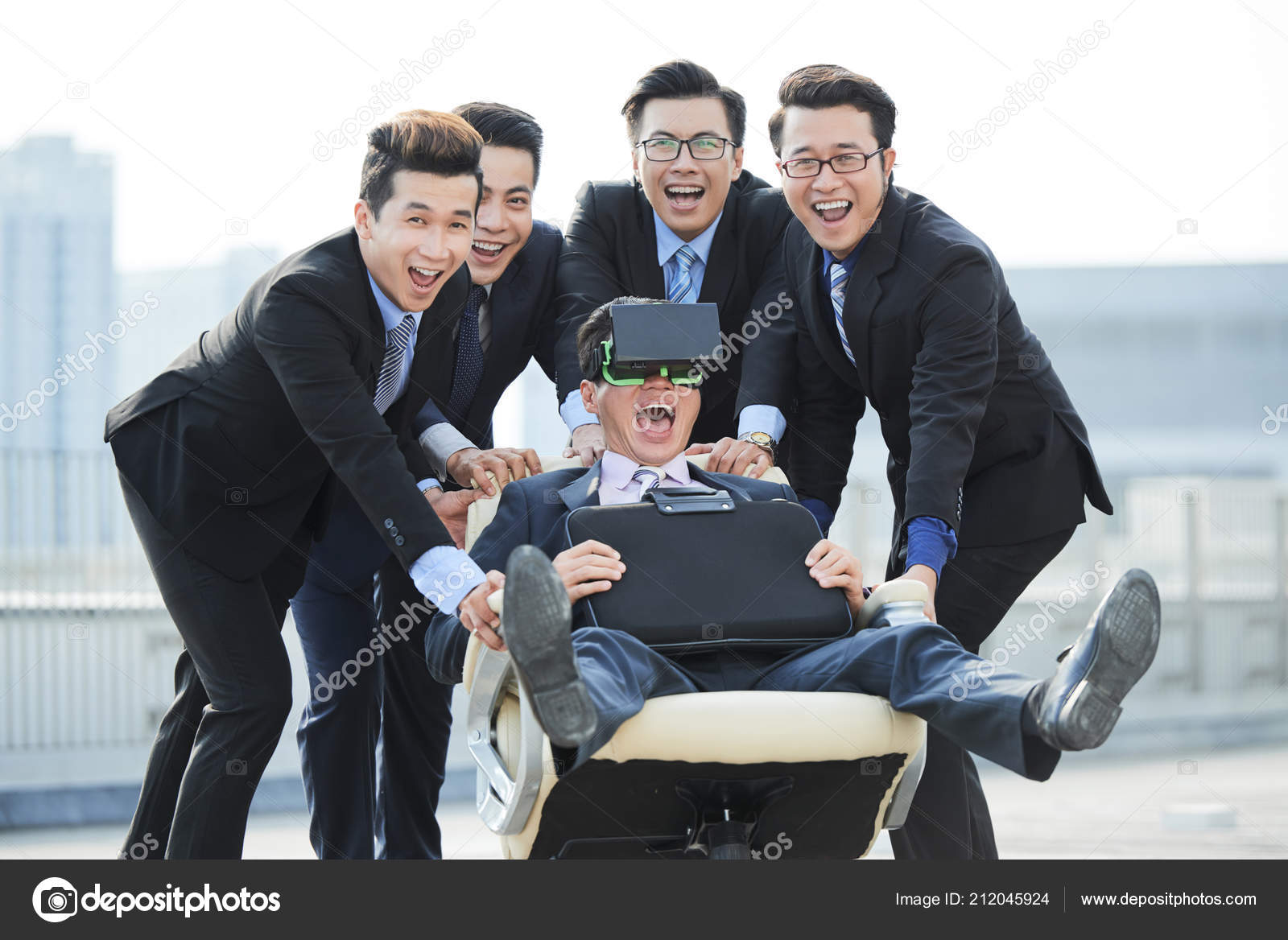 swivel chair vr king louis xvi dining chairs joyful asian businessmen pushing colleague wearing with headset photo by dragonimages