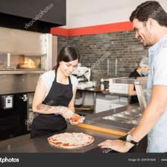 Kitchen Prep Station Wicker Chairs 美丽的厨师准备香肠比萨为客户站在厨房柜台在比萨店 图库照片 C Tonodiaz