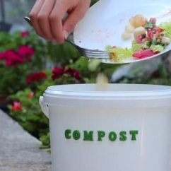 Compost Bin For Kitchen Cabinets Manufacturers 年轻的白种人把剩下的盘子扔到堆肥箱里堆肥降解食品废弃物再利用施肥土壤 年轻的白种人把剩下的盘子扔到堆肥箱里堆肥