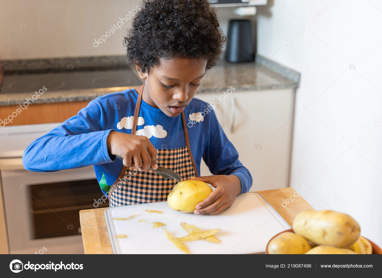 kitchens to go top rated kitchen stoves 小黑男孩打扮成厨师在厨房去皮土豆 图库照片 c danillao 219087496
