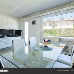 Kitchen Glass Table And Chairs 白色厨房与黑色大理石和典雅的玻璃桌和皮革椅子里面没人 图库照片