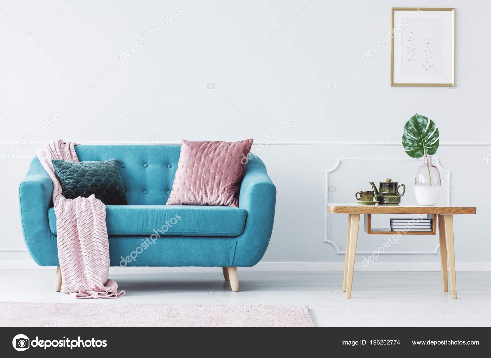 coussin rose sur canape turquoise cote table bois pastel salon photo