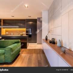 Kitchen Clocks Floor Mats Washable 现代典雅起居室内带花瓶和钟表的木制橱柜绿色天鹅绒沙发和深色厨房角落 照片作者photographee Eu
