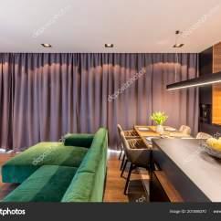 Kitchen Table Nook Cleaning 绿色角落沙发在灰色公寓内部与厨房海岛在光旁边在餐桌附近 图库照片