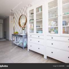 Kitchen Console Table Knobs And Pulls 白色厨房橱柜与柔和的菜和蓝色控制台桌站立在真正相片房子内部与图案的 白色厨房橱柜与柔和的菜和蓝色控制台桌站立在真正