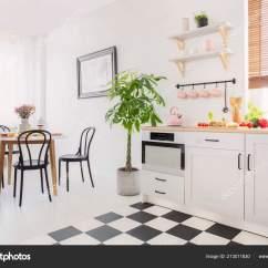 Small Kitchen Table Set Floating Cabinets 餐桌上的黑色椅子上有白色扁平的花朵旁边是小厨房的植物真实照片 图库 餐桌上的黑色椅子上有白色扁平的花朵旁边是小厨房的