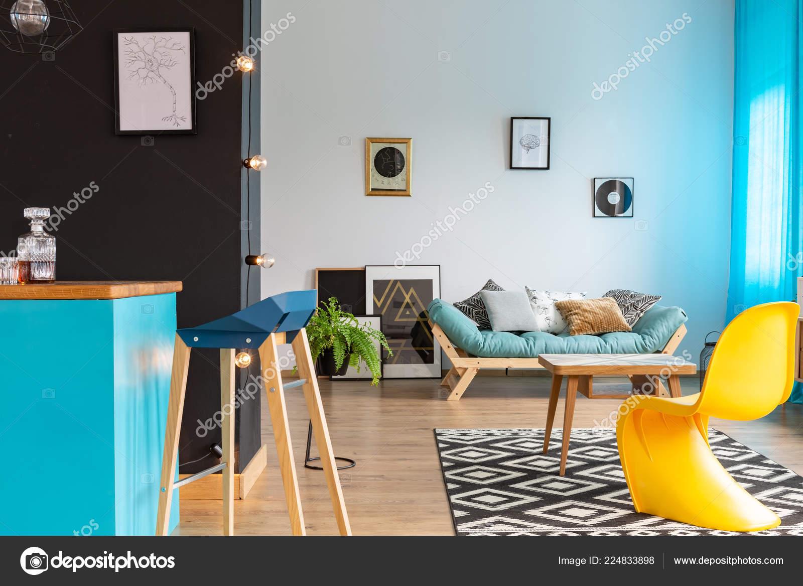 blue kitchen chairs faucets review 现代黄色椅子在兼收并蓄的客厅与蓝色厨房岛黑色的墙壁和舒适的沙发与海报 现代黄色椅子在兼收并蓄的客厅与蓝色厨房岛黑色的墙壁和