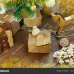 Beautiful Christmas Gifts In Different Packaging Toys Wooden Horse Birds And Cookies Under The Branches Of