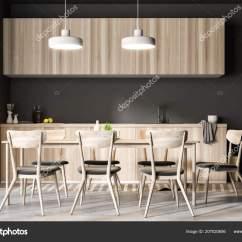 Concrete Kitchen Table Birch Cabinets 餐厅和厨房内部有灰色的墙壁一个混凝土地板一个长桌子椅子和木台面前视图 餐厅和厨房内部有灰色的墙壁一个混凝土地板一个长桌子椅子和