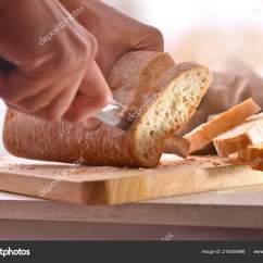 Kitchen Benches Cost Cabinets 厨师在厨房长椅上的切板上切片面包前视图水平组合 图库照片 C Davizro