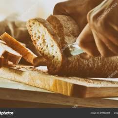 Kitchen Benches Silver Cabinet Knobs 厨师在厨房长椅上的切板上切片面包前视图水平组合 图库照片 C Davizro