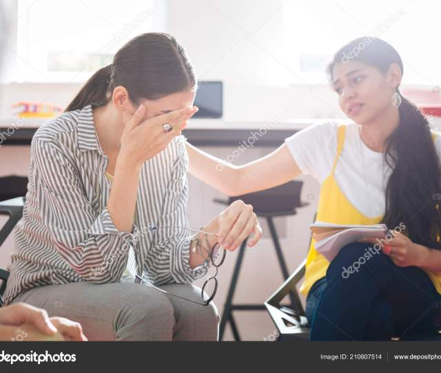 Kind Girl Looking At The Crying Person And Showing Her Support And Understanding Stock Photo