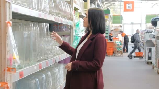 kitchen goods store cabinets portland young girl chooses glass vase in the section of dishware hypermarket customer shopping housewares buying