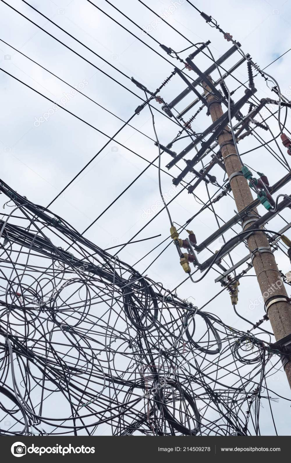 medium resolution of telephone pole and chaotic mess of wires against sky stock photo