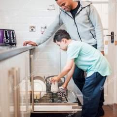 Kitchen Aid Bowls Modern Table 小男孩正在帮助他的父亲在家里装洗碗机 图库照片 C Dglimages 204330298