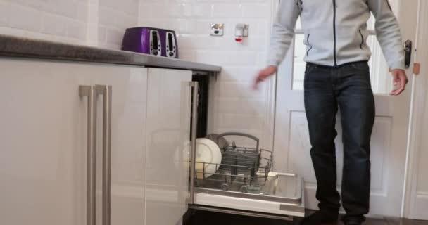 kitchen aid bowls pendant lighting over island 中年男子正用他儿子的帮助把洗碗机放在家里的厨房里 图库视频影像 中年男子正用他儿子的帮助把洗碗机放在家里
