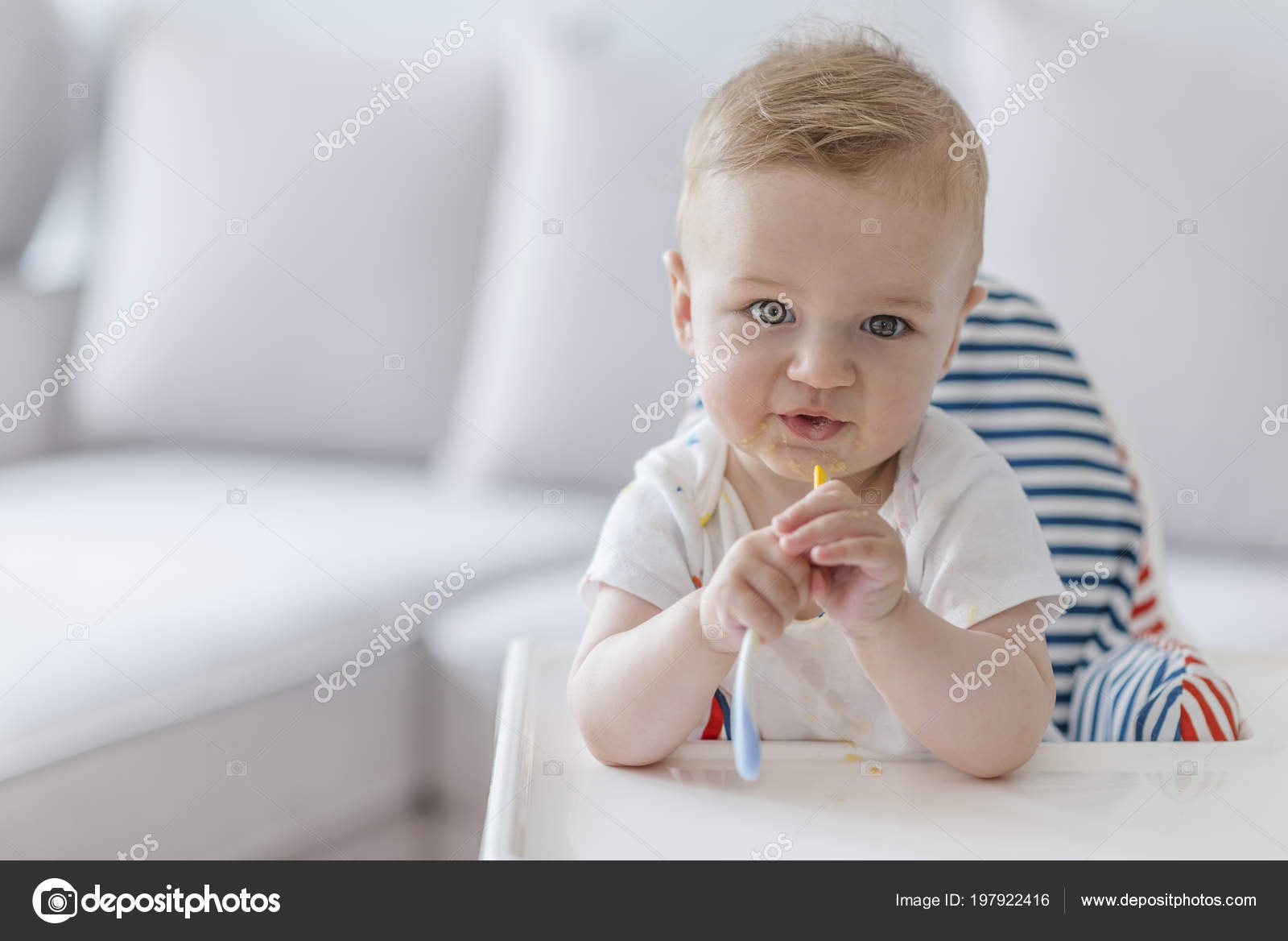 high chairs for small babies affordable desk baby sitting highchair all messy eating orange food spoon in with mouth child sits on a chair and