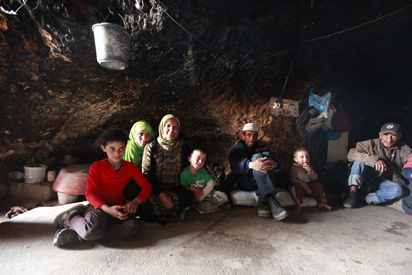 Family of Fadel Hamamdi gathered in their home. The caves are usually divided into three areas: a living area, a storage and cooking area, and one for livestock in winter.