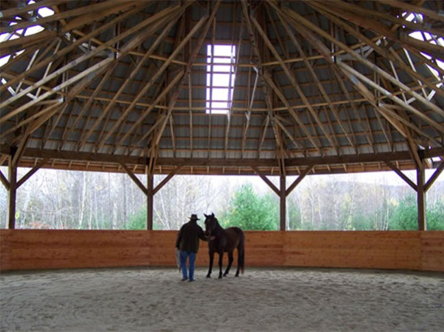 A horse working in the covered round pen