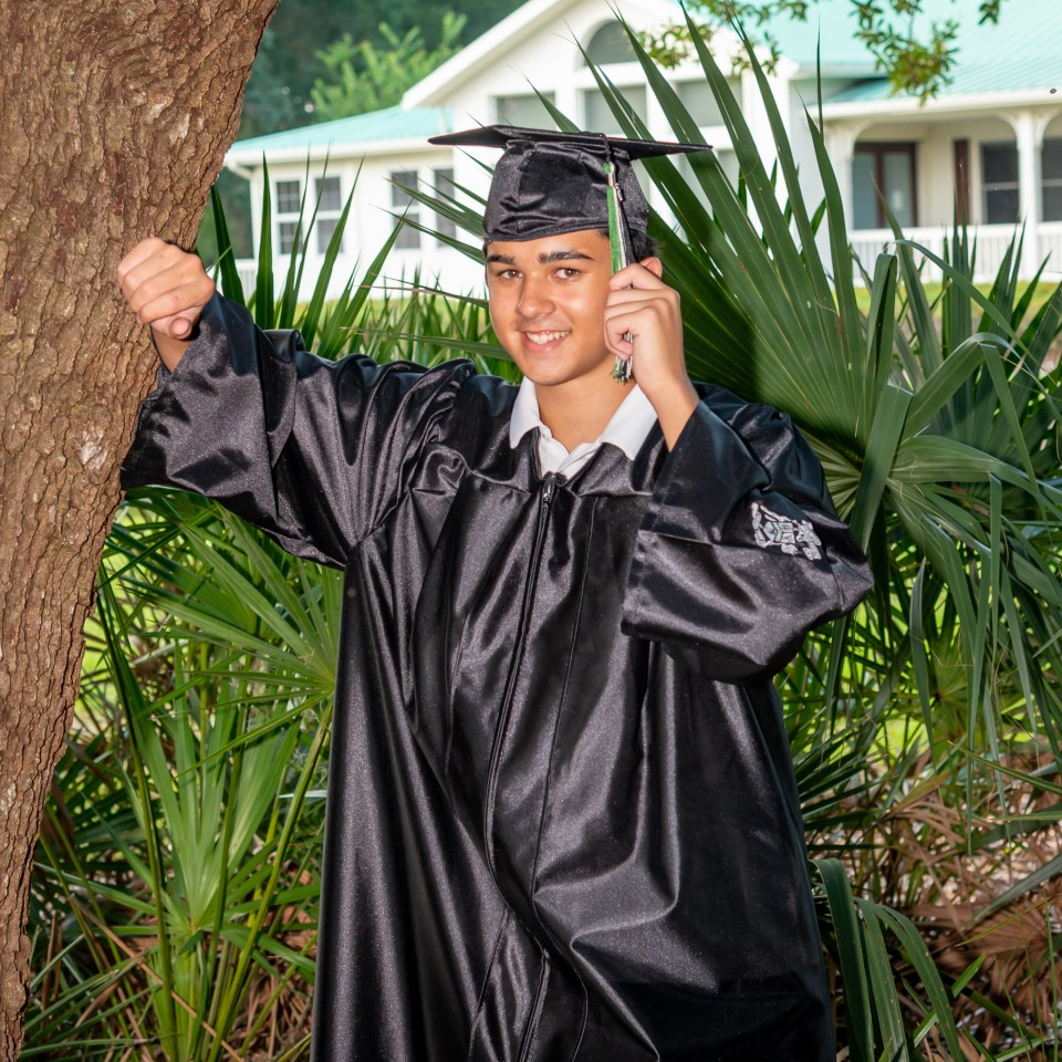 A senior in his cap and gown holds his tassel on the left to signify he has graduated