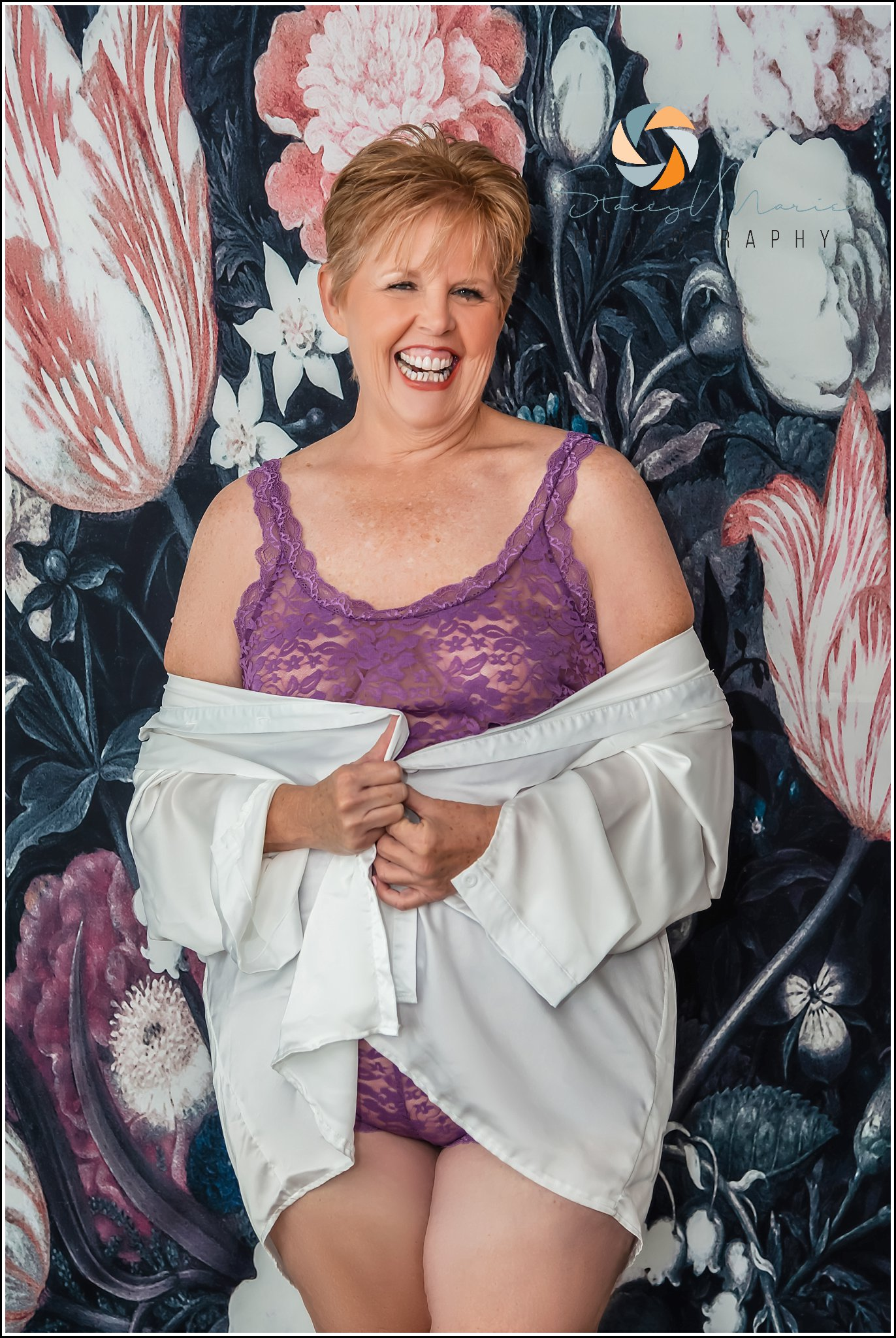 An older woman, stepping out of the box, poses in purple lingerie and a silk shirt for her boudoir session.