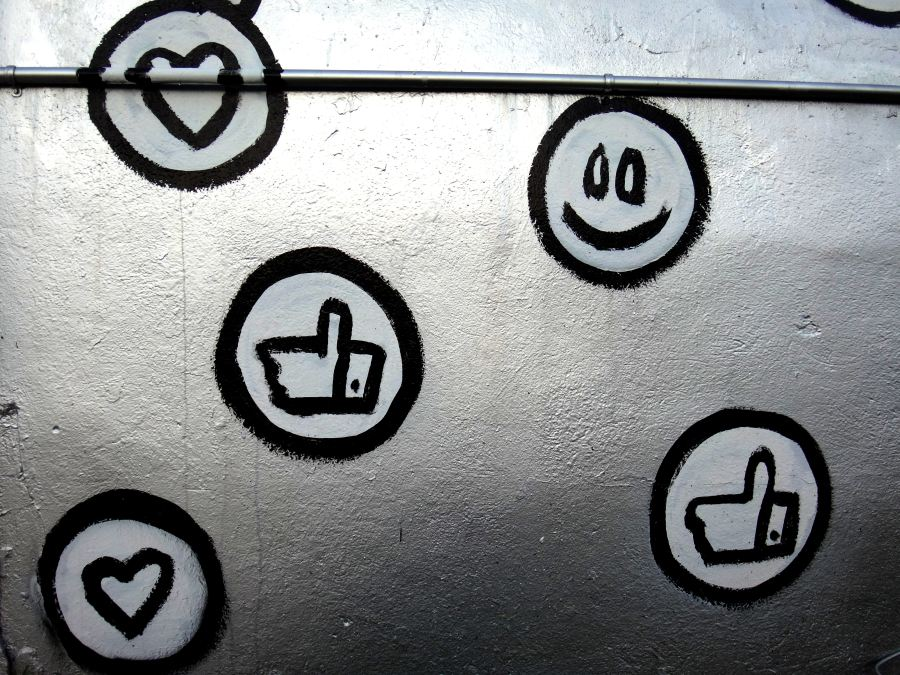 Graffiti style social media icons - heart, thumbs up and smiley face. Painted in black and white on a silver background