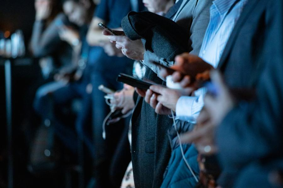 A row of people in suits all looking at their smart phones - picture is a close up of their hands.