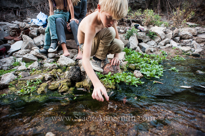Color photograph of a boy playing in a creek near Denver