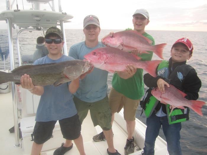 Stacy Harris' Boys: Howlett, Hampton, Hunter, and friend Zane holding up their catch!