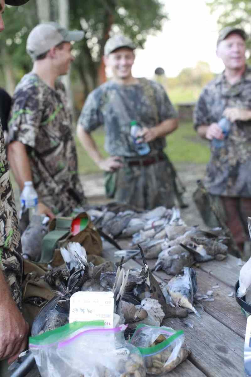 All the participants of the dove hunt gathered around the table covered in mourning doves