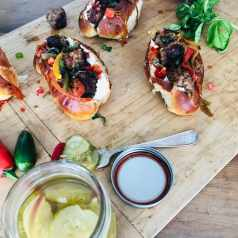 A picture of Venison Meatball Rolls with Horseradish mayonnaise being prepared on a wooden slab, with pickles. Recipe by Stacy Lyn Harris