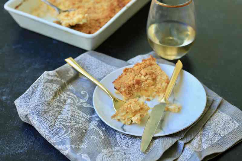 horizontal photo of squash casserole in dish with fork holding a bite. White wine and casserole are in background.