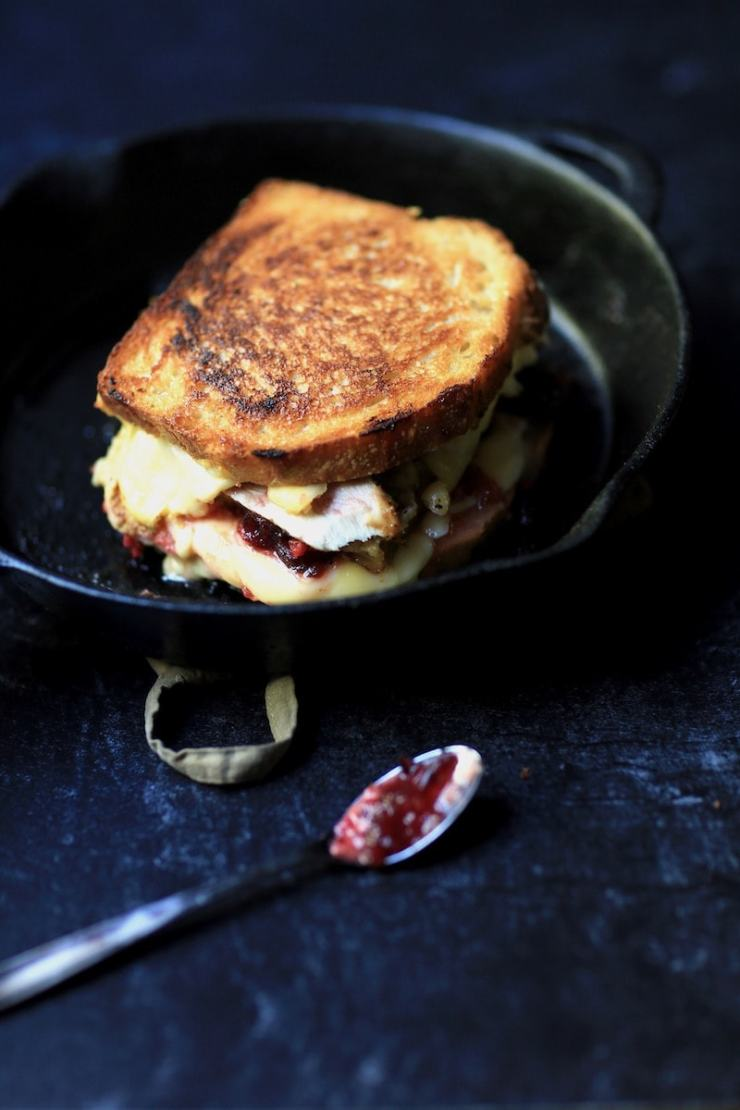 Whole Turkey, Dressing, Cranberry, Cheese Sandwich in Cast Iron Skillet on Dark Background with spoon
