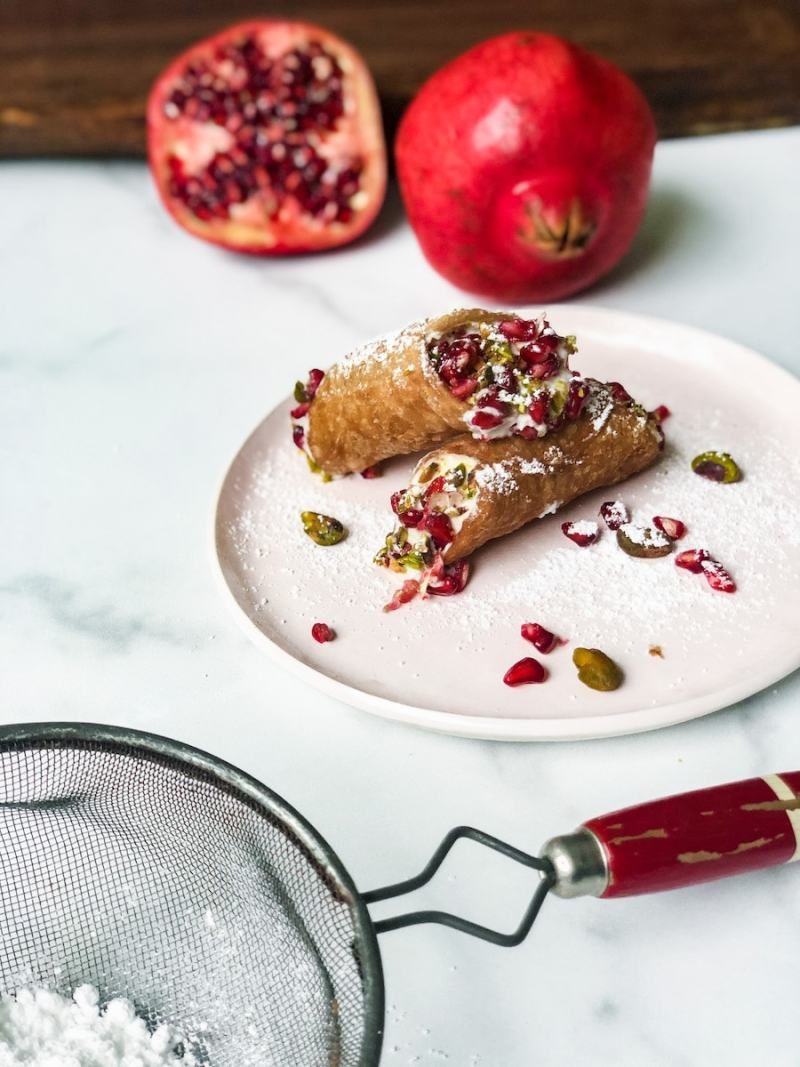 Cannoli with pomegranates in background on marble