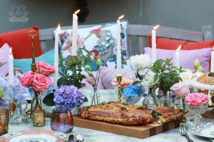 Kale Pastry Recipe surrounded by candles, flower arrangements, pillows in the seats and a table dressed in linen